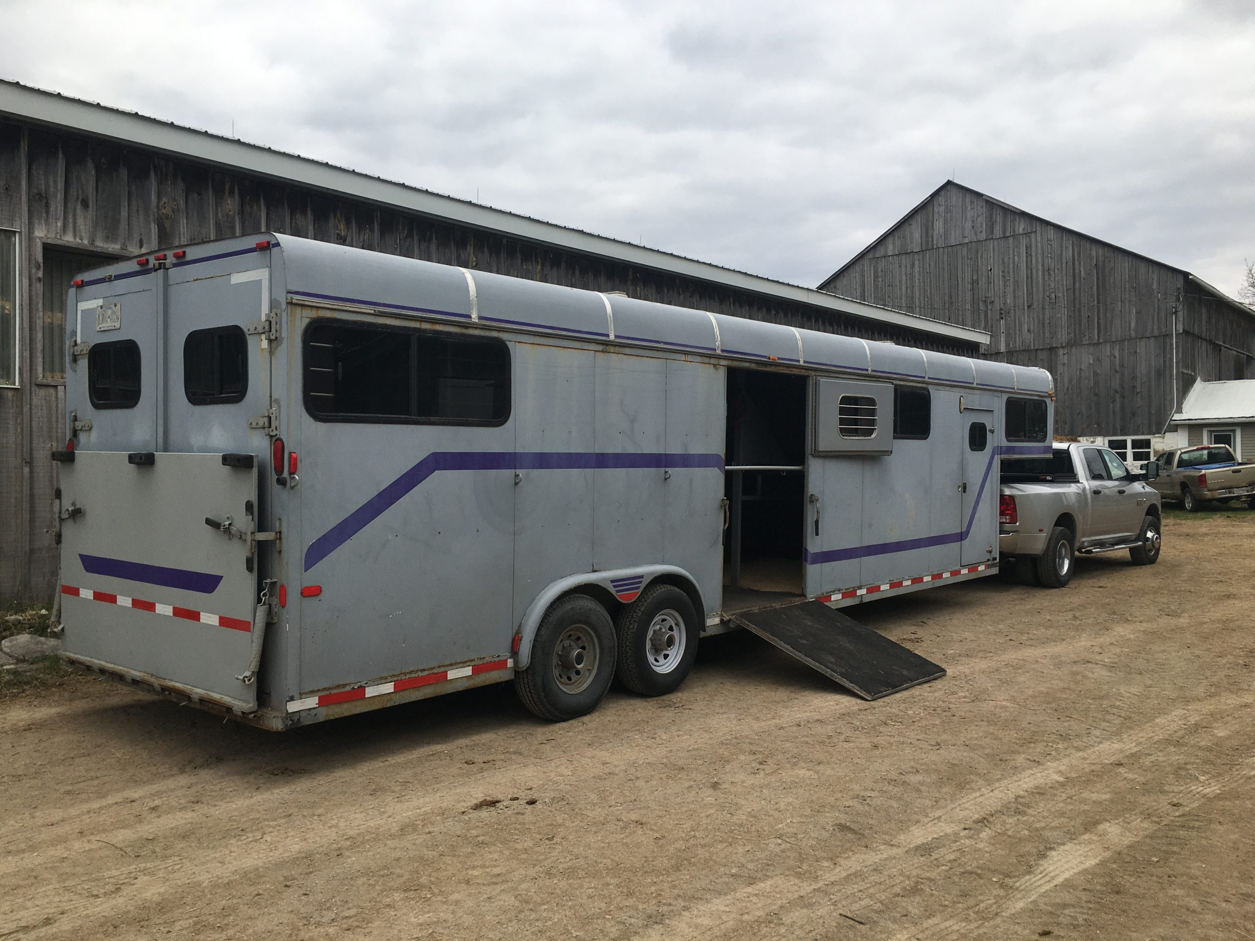 Horse trailer and truck by barn